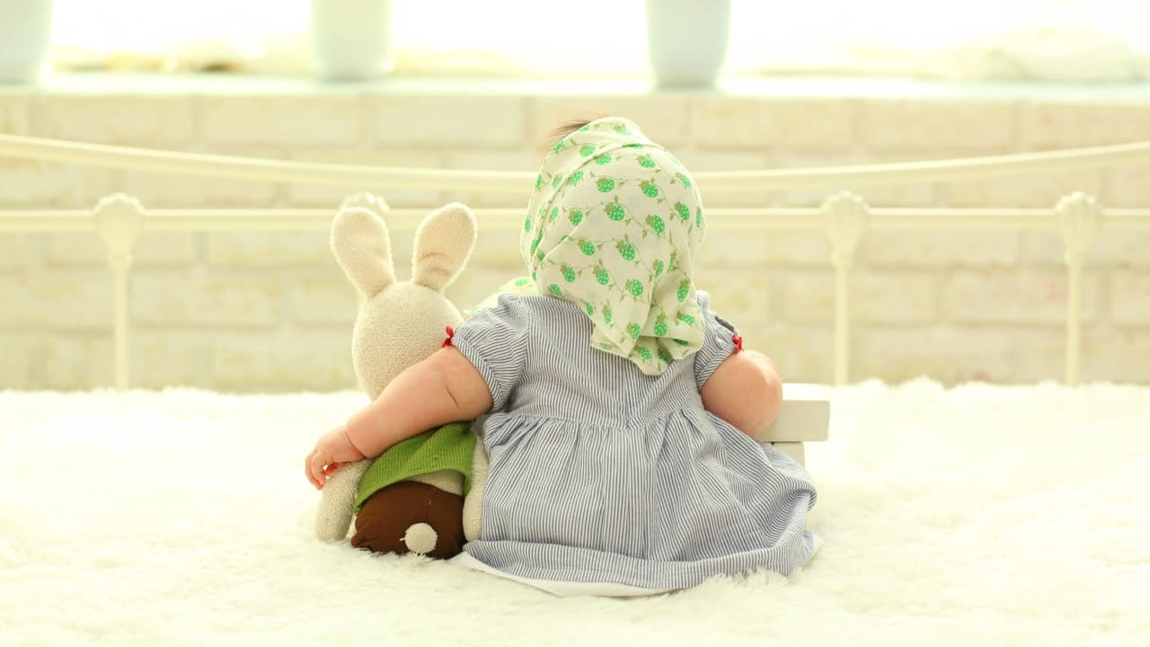 ぬいぐるみと赤ちゃんの後ろ姿